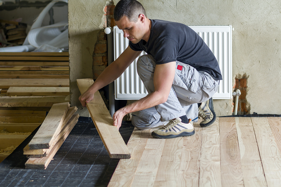 professional carpenter installing natural wooden planks on wooden frame floor in empty unfinished room under reconstruction. Improvement, renovation and carpentry concept