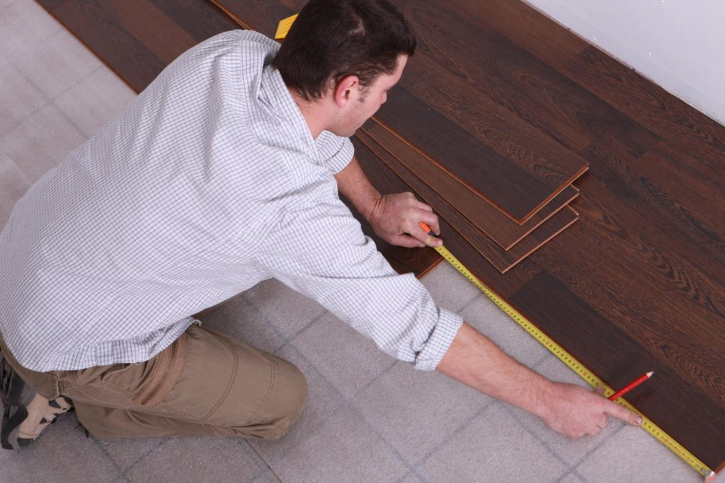 male worker measuring the wood flooring